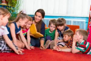 Children with tutor reading book at kindergarten