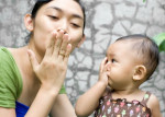 Mom and baby blowing kisses