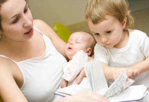 Mom with two young kids reading