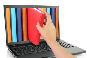 hand pulling a book out of a computer screen