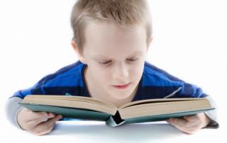 school age boy reading book