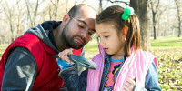 father and daughter with magnifying glass