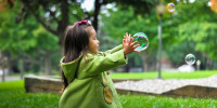 girl reaching for bubbles