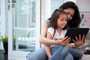 mother and child reading tablet