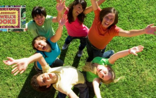 Teens in a circle with their hands in the air