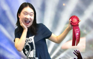 Teen girl holding up a ribbon with excited look