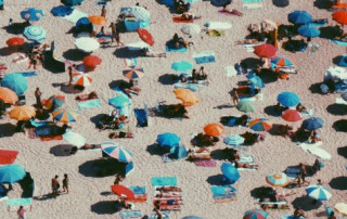 People with umbrellas at a crowded beach
