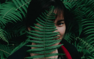 girl behind fern leaf