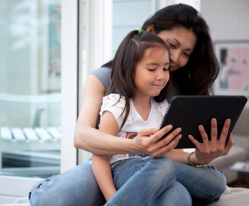 Mother sitting with daughter looking at a tablet device.