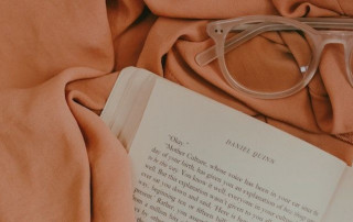 Book and eyeglasses on bed. Photo by Vanessa Serpas on Unsplash