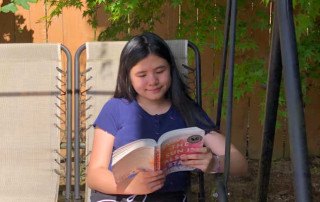 Teen girl reading a book outside