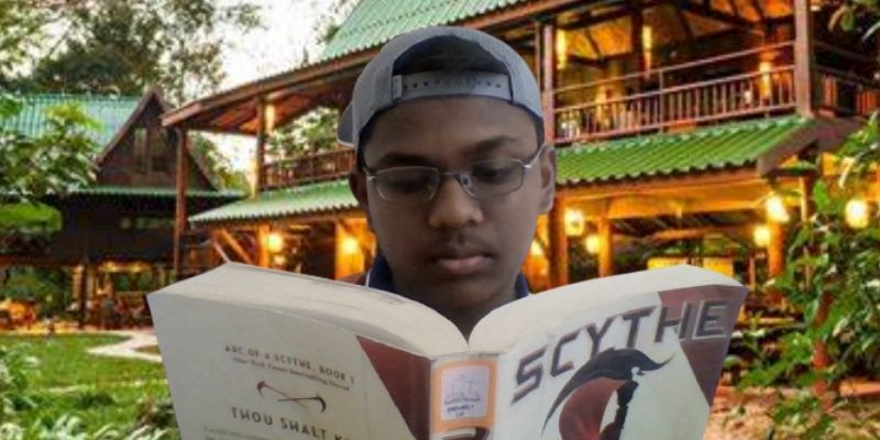 Teen boy with backward baseball hat reading a book in front of a lodge